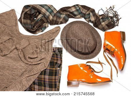 British fashion style women outfit of plaid pants, knit sweater, trilby hat, scarf and orange patent leather lace up shoes with tapered toes