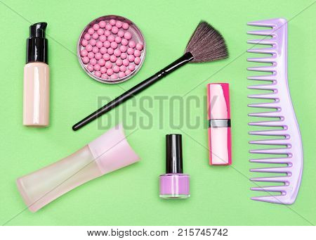 Modern woman essentials: foundation, blush, lipstick, perfume, nail polish, comb. Cosmetic bag must-haves. Top view, flat lay