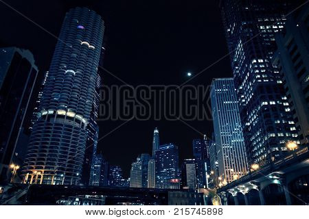 Night cityscape in Chicago with tall high-rise buildings, marina towers, river train bridge, promenade and moon.