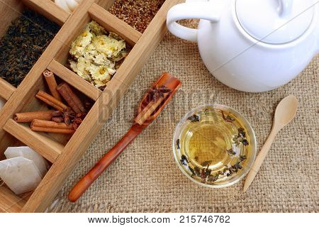 Tea time set,dried tea leaves,dried yellow chrysanthemum flowers ,cinnamon in wooden box and tea pot with China tea with wooden spoon on sack cloth,top view