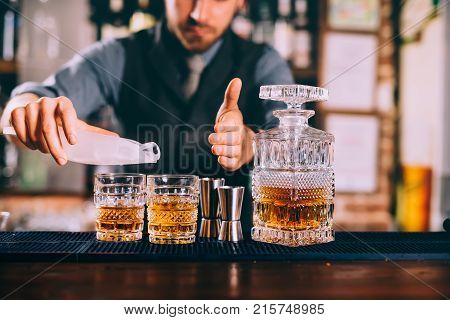 Close Up Of Barman Hands Adding Ice And Whiskey To Modern Urban Cocktails. Sky Bar Serving Elegant D