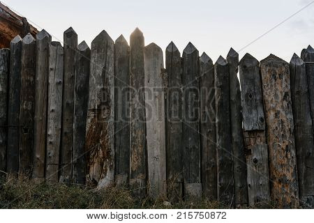 Wooden fence of thick logs with sharp peaks