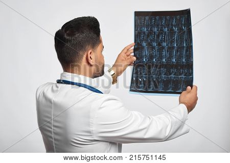 Rearview shot of a male doctor in white labcoat examining an x-ray or MRI scan on gre background at studio profession occupation job experience trustworthy medicine research health people.