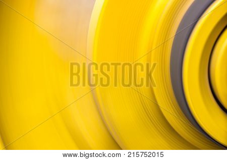 Big yellow pulleys are rapidly rotating by being driven by a conveyor belt.
