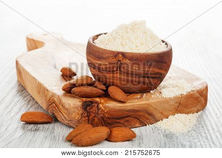 Almond flour and almonds on wooden cutting board.