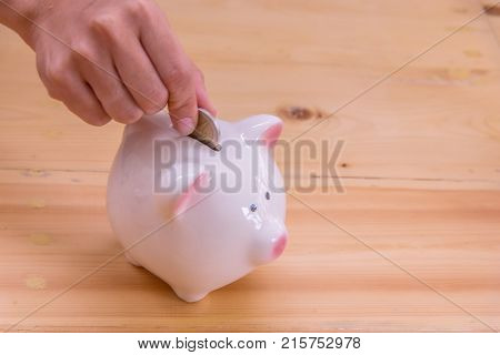 Coins on hand are dropped Piggy bank on wooden top table money savings concept