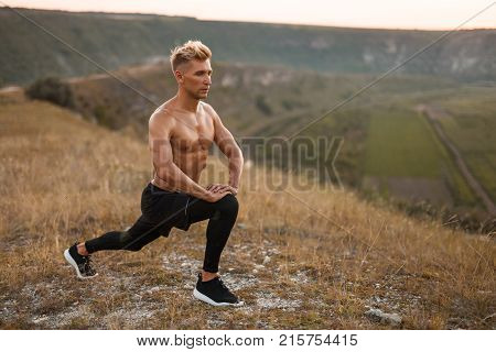 Bare-chested man performing lunges during his training in nature.