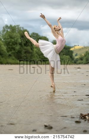 Attractive ballerina posing on the left toe in the shallow river on the background of green shore and cloudy sky. She wears a white tutu, pink leotard and beige pointes. Her arms outstretched upward.