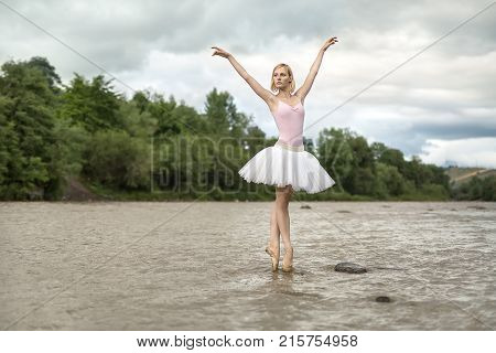 Charming ballerina stands on the pointes in the shallow river on the background of green shore and cloudy sky. She wears white tutu, pink leotard and beige ballet shoes. Her arms outstretched upward.