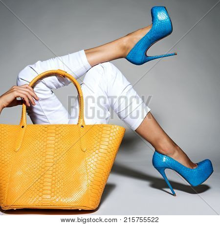 Closeup photo of female style leather bag. Part of women legs in beautiful fashionable high heels.