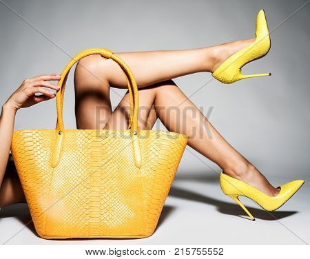 Closeup photo of female style yellow leather bag. Part of women legs in beautiful fashionable high heels.