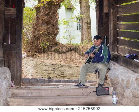 Sighisoara Romania October 08 2017 : The street guitar player plays the guitar near the entrance to the tunnel leading to the old town of Sighisoara in Romania