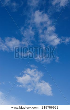 A clear blue sky with sparse white fluffy clouds