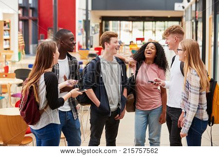 Student Group Socializing In Communal Area Of Busy College