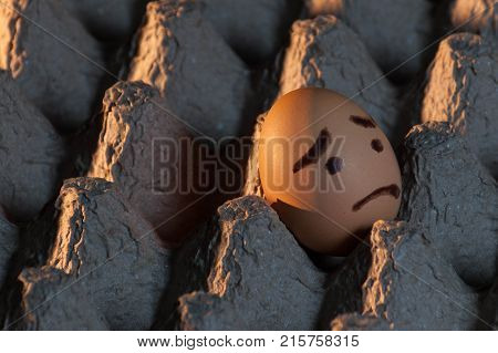An egg with a sad face painted on it alone in a cardboard egg tray looking out of the frame