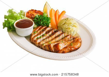 White isolated background with clipping paths homemade pork steak or barbecue slices on white plate. Pork steak served with mash potato barbecue sauce and vegetable. Delicious pork barbecue or pork steak for lunch or dinner. Mexican food.