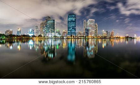 Dusk scence of Bangkok Panorama Aerial view of Bangkok modern office buildings and condominium in Bangkok city downtown with dusk sky and clouds at Bangkok Thailand. And Reflection on Lake.
