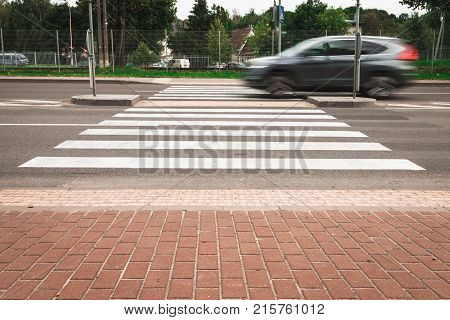 A grey car at high speed crosses a pedestrian crossing, a blur effect. Street racing.