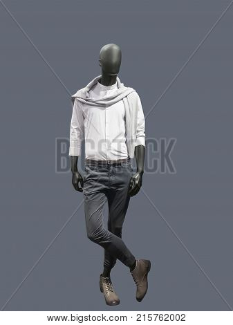 Full-length male mannequin dressed in casual clothes over gray background. No brand names or copyright objects.