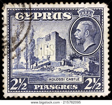 LUGA RUSSIA - OCTOBER 17 2017: A stamp printed by CYPRUS shows image portrait of King George V and view of Kolossi Castle - a former Crusader stronghold in Kolossi village circa 1934