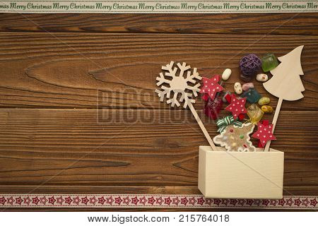 A beige box, gingerbread, wooden Christmas toys and colored candies on a rustic wooden table. A star patterned ribbon on the bottom. A Merry Cristmas inscription ribbon at the top. Christmas background. Copy space. Top view