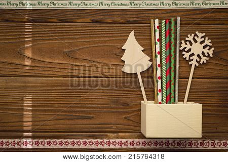 A beige box, gingerbread, wooden Christmas toys and colored straws with patterns. A star patterned ribbon on the bottom. A Merry Cristmas inscription ribbon at the top. Christmas background. Copy space. Top view