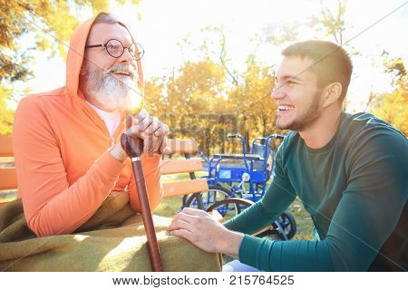 Young caregiver with senior man in park