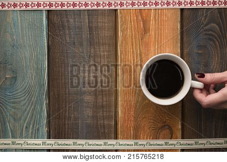 A colored wooden Christmas background with hand holding a cup. A star patterned ribbon at the top. A Merry Cristmas inscription ribbon on the bottom. Copy space. Top view