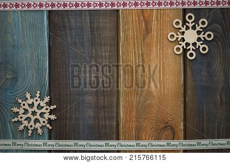 A colored wooden Christmas background with wooden snowflakes. A star patterned ribbon at the top. A Merry Cristmas inscription ribbon on the bottom. Copy space. Top view
