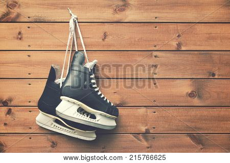 ice hockey skates hanging on nail on wooden plank background