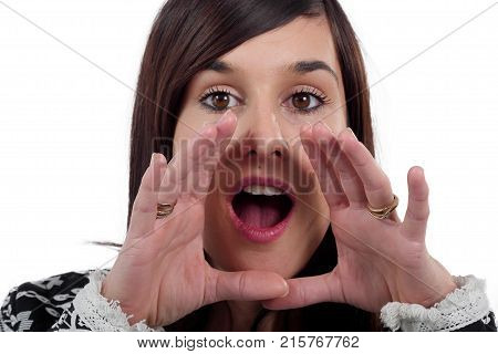 woman yelling with hands next to the mouth on white