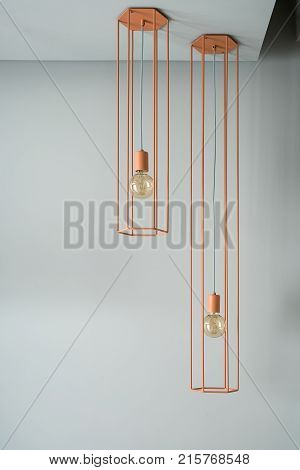 Two hanging metallic orange lamps with edison light bulbs on the gray wall background indoors. One lamp is longer than other. Closeup vertical photo.