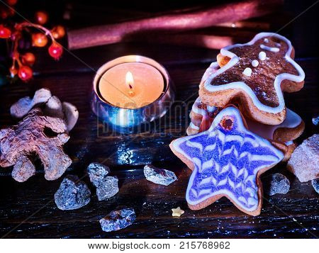 Candle light table with Christmas gingerbread cookies and cinnamon stick and star sweets are on wooden table and burning candles. Xmas still life object. Cookie is slide.