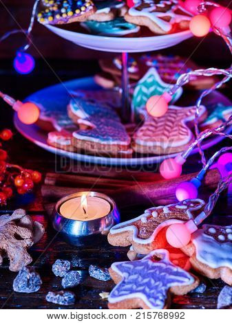 Candle light table with Christmas gingerbread cookies and Xmas garland and star sweets decoration tiered cake stand on table and burning candles. Close-up.