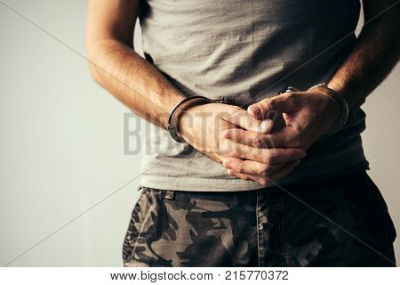 Handcuffed soldier in military army clothes. Prisoner of war or arrested close up of hands in handcuffs selective focus.