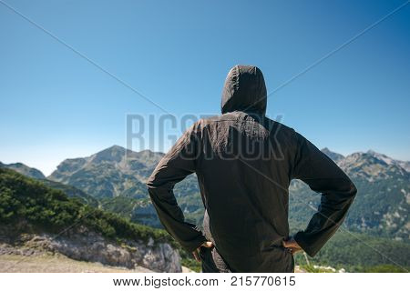 Mountain hiker at high viewpoint looking at the valley. Male tourist person in hooded jacket at mountain top enjoying the view.