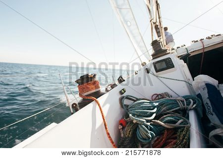 Deck of professional sailboat or racing yacht during competition on sunny and windy summer day moving fast through waves and water with spinnaker up and ropes tied around winch