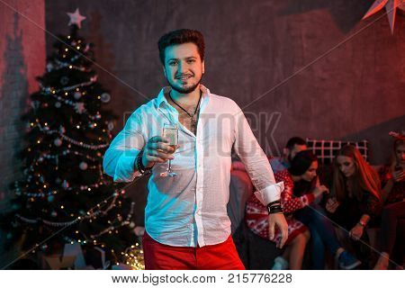 Christmas, x-mas, New year, winter, happiness concept - smiling man with a glass of champagne. Funny people. Christmas party at home