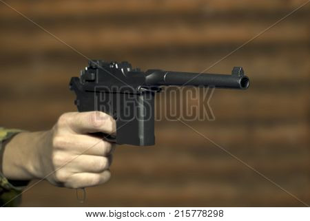 A man's hand with a vintage semi-automatic pistol points past the frame on the background of a log wall. Focus on the muzzle of the pistol the rest is blurry.