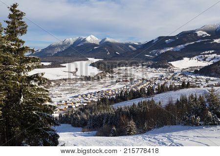 Zuberec ski resort; Western Tatras. Slovakia. View from ski slopes to the snowy valley and village against the backdrop of the mountain peaks. Winter landscape. Destination for the winter holidays. Concept of winter recreation sports healthy lifestyle