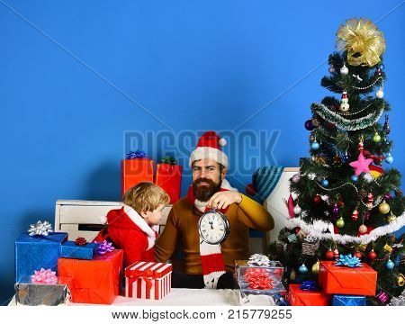 Happy Kid And Santa In Hat Holding Old Wooden Clock