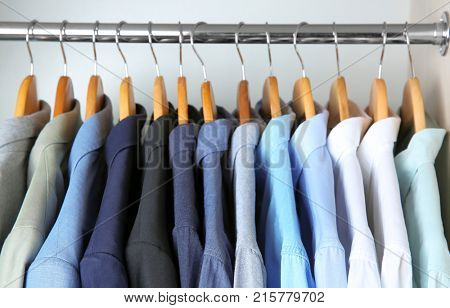 Male jackets and shirts hanging on clothing rail in wardrobe