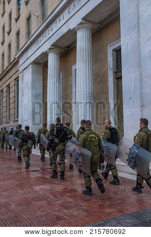 ATHENS, GREECE - NOVEMBER 18 2017: Riot police with their shield, take cover during a rally in front of Athens University, which is under occupation by protesters leftist and anarchist groups.