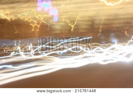 Abstract Lights Background with Vibrant Soft Yellow, Golden and White Light Lines and Trail Patterns. Long Exposure Design Image of City Street at Night. Electrical Discharge Flash Glow Illusion.