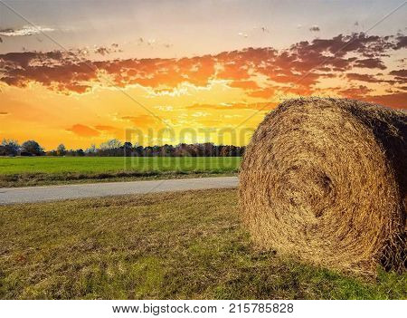 A closeup of a round bale of hay out in a field by a road under a beautiful golden sunset. Copy space.