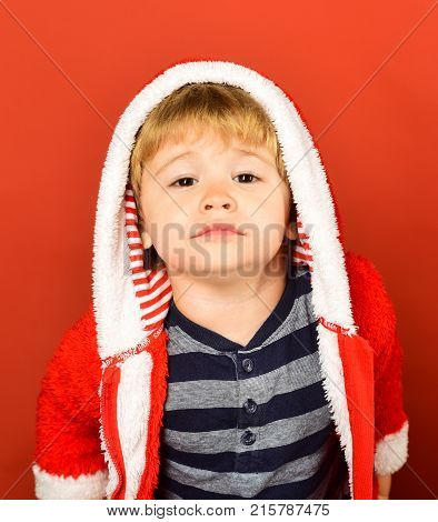 Xmas holiday concept. Kid with cute smile on Christmas eve. Child with enthusiastic face on red background. Boy in xmas hoodie poses in close up
