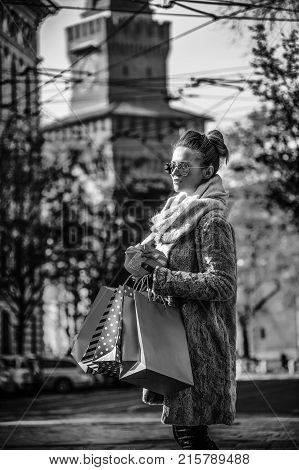 Rediscovering things everybody love in Milan. young woman with shopping bags and Christmas gift near Sforza Castle in Milan Italy looking into the distance