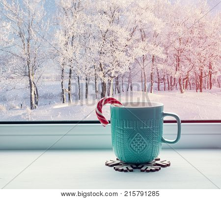 Winter background - cup with candy cane on windowsill and winter forest outdoors. Cozy winter still life with concept of spending winter indoors with Christmas and New Year winter mood. Winter still life, cozy winter composition