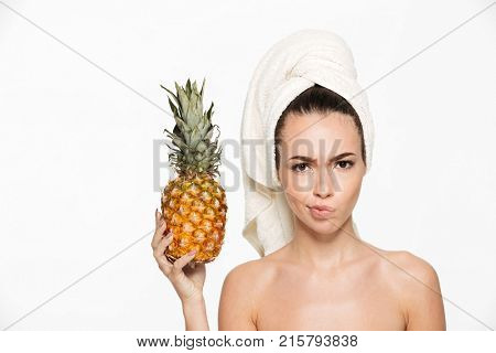 Beauty portrait of an upset unsatisfied half naked woman with a towel wrapped around her face holding pineapple and looking at camera isolated over white background