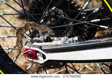 A close-up of the disc rear brakes of an off-road enduro motorcycle. The concept of motorsport